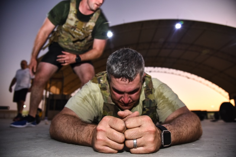 A U.S. Air Force Airman does burpees over his partner during the EOD 134 Memorial Workout at Al Dhafra Air Base, United Arab Emirates, Nov. 30, 2018. 380th Air Expeditionary Wing Airmen, along with coalition partners, participated in the workout to honor the 134 EOD technicians from the U.S. Air Force, Army, Navy and Marine Corps that have been killed since Sept. 11, 2001. (U.S. Air Force photo by Senior Airman Mya M. Crosby)