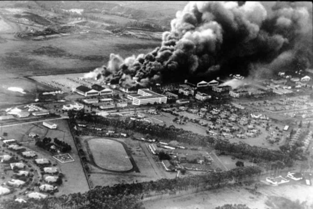 Aerial photo of Wheeler Field during the early phase of the Pearl Harbor attack. Multiple P-36s and P-40s (left center) still sit undamaged as the base sustains heavy bombardment. (National Archives photo)