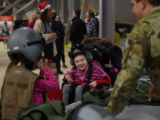 Guests of the492nd Fighter Squadron Christmas Party try on pilot's helmets and gear at the Duxford Imperial War Museum, Cambridge, England, Dec. 1, 2018. Around 50 members and spouses from the 492nd FS 'Madhatters' collaborated with the three charity organizations to help bring some extra joy this holiday season to children with serious or terminal illness or severe burns. (U.S. Air Force photo by Staff Sgt. Alex Fox Echols III)
