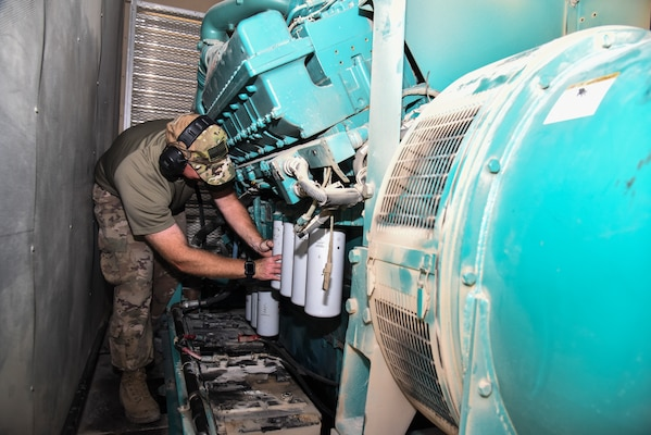 U.S. Air Force Staff Sgt. Tyler Muldowney, 380th Expeditionary Civil Engineer Squadron electrical power production craftsman, provides preventative maintenance on an oil filter of a generator at Al Dhafra Air Base, United Arab Emirates, Nov. 19, 2018. The Power Production flight provides two main capabilities: maintaining power generators for buildings across the installation, and ensuring the integrity of the fighter aircraft arresting barrier systems on the flight line. (U.S. Air Force photo by Senior Airman Mya M. Crosby)