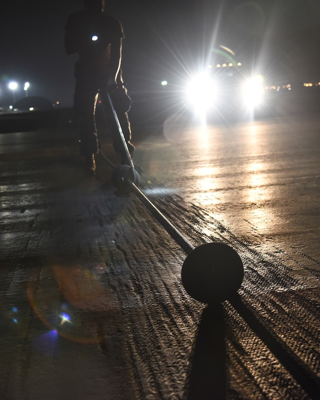 U.S. Air Force Senior Airman Jacob Cornelius, 380th Expeditionary Civil Engineer Squadron electrical power production and barrier maintenance journeyman, ensures precise spacing in between cable donuts of a BAK-12 Aircraft Arresting System at Al Dhafra Air Base, United Arab Emirates, Nov. 24, 2018. The Power Production barrier maintenance shop's job centers on a 195-foot-long cable that assists in the case of a fighter jet in need of an emergency landing at ADAB. (U.S. Air Force photo by Senior Airman Mya M. Crosby)