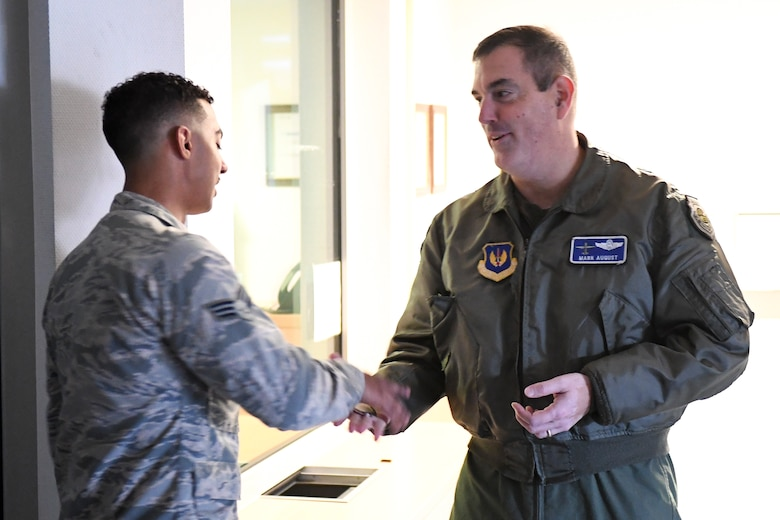 U.S. Air Force Brig. Gen. Mark R. August, 86th Airlift Wing commander, presents a coin to U.S. Air Force Senior Airman Cadairo Domino, 86th Security Forces Squadron installation patrolman, on Ramstein Air Base, Germany, Dec. 6, 2018. Domino received the honor of being Ramstein's Airlifter of the Week for assisting a pregnant mother through active labor during entry controller duties in late October. (U.S. Air Force photo by Staff Sgt. Devin Boyer)