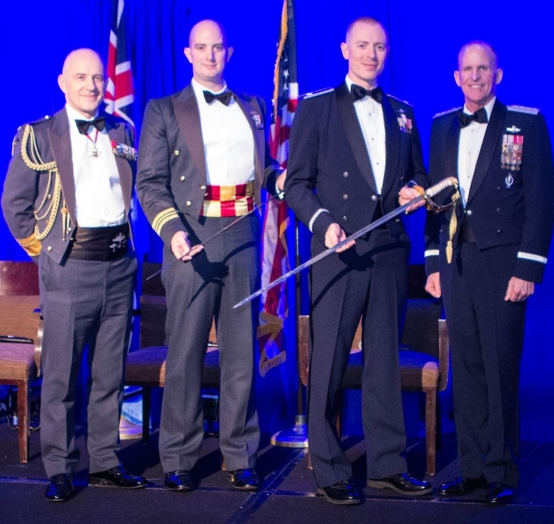 Air Marshal Stuart Atha, Deputy Commander Operations Royal Air Force(RAF), Sqn Ldr Benjamin Durham, RAF Sword of Honour winner, Lt. Col. Gwyddon Owen, U.S. Air Force Sword of Honour Winner, Gen. Stephen Wilson Vice Chief of Staff U.S. Air Force, stand on stage during the Royal Air Force Museum American Foundation (RAFMAF) Sword of Honour ceremony, Oct. 11, 2018.  According to the RAFMAF, the award is presented to a Royal Air Force (RAF) and U.S. Air Force (USAF) Exchange Officer each year whose contributions have most reflected the values that honor the veterans and the Foundation share: service, excellence, integrity and courage. (Courtesy photo/Royal Air Force Museum American Foundation)