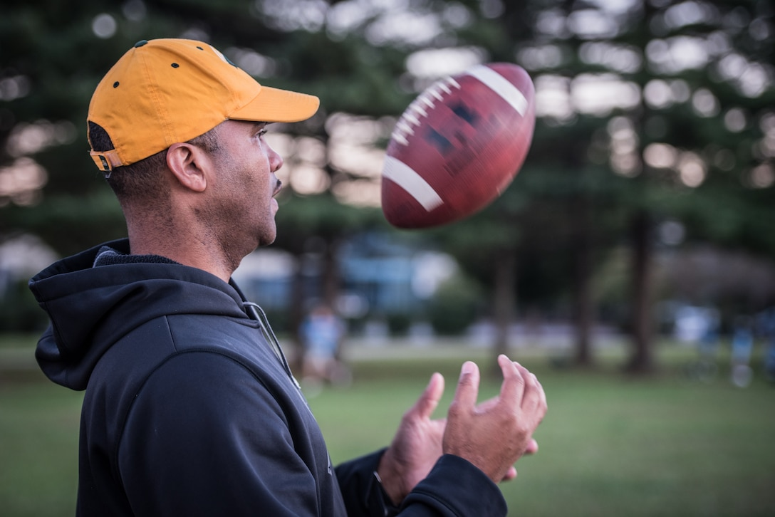 Chief Master Sgt. Anthony Harris, 512 Airlift Wing Force Support Squadron superintendent, tosses a football in Dover, Delaware, Oct. 18, 2018. Harris coaches The Pop Warner Dover Caesar Rodney Raiders peewee league team. (U.S. Air Force photo by Staff Sgt. Damien Taylor)