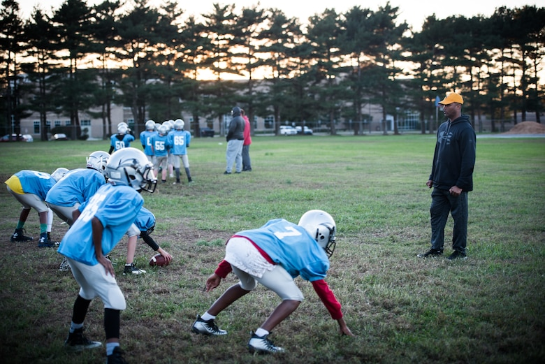 Chief Master Sgt. Anthony Harris, 512 Airlift Wing Force Support Squadron superintendent, drills four peewee league football players in Dover, Delaware, Oct. 18, 2018. Harris was the secondary defensive coach for the Pop Warner Dover Caesar Rodney Raiders during the four-month 2018 season. (U.S. Air Force photo by Staff Sgt. Damien Taylor)