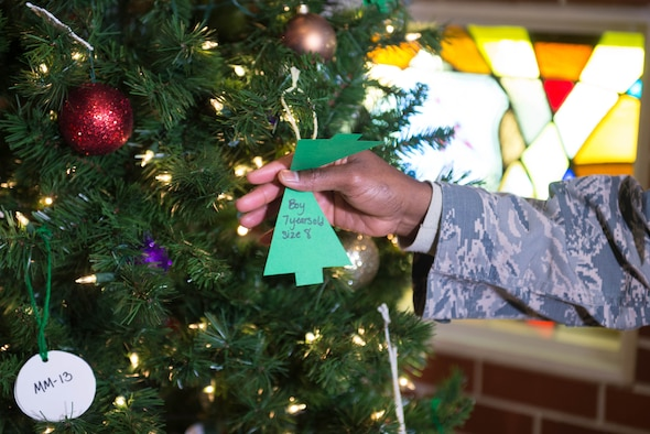 Capt. Matthew Brantley, 55th Wing chaplain, opens a tags on an Angel Tree in Strategic Air Command chapel Dec. 6, 2018, at Offutt Air Force Base, Nebraska. Each year, Team Offutt members pull ornaments from the base chapels with a child's description and their desired gift, and purchase the gift to be given anonymously. (U.S. Air Force photo by Zachary Hada)