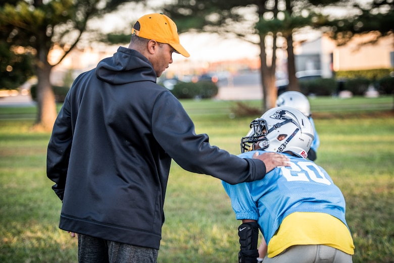 Chief Master Sgt. Anthony Harris, 512 Airlift Wing Force Support Squadron superintendent, sets a hand on his son, Anthony's, shoulder on a field in Dover, Delaware, Oct. 18, 2018. Harris has coached his son as a Pop Warner Dover Caesar Rodney Raider from 2016 - 2018. (U.S. Air Force photo by Staff Sgt. Damien Taylor)