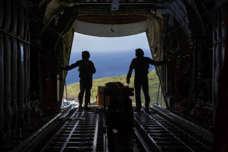 Two service members overlook the ocean in an aircraft ready for a practice drop.