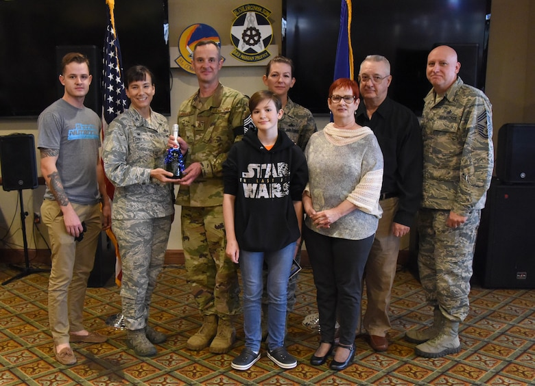 U.S. Air Force Col. Debra Lovette, 81st Training Wing commander, and Chief Master Sgt. David Pizzuto, 81st TRW command chief, presents Senior Master Sgt. Charles Sargent, 338th Training Squadron flight chief, and his family with a memento for his promotion to the rank of chief master sergeant at Keesler Air Force Base, Mississippi, Dec. 6, 2018. Five senior master sgts. at Keesler were selected for promotion. (U.S. Air Force photo by Kemberly Groue)