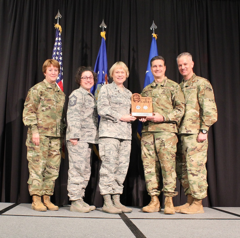 """U.S Air Force Lt. Gen. Dorothy Hogg, Air Force Surgeon General, U.S. Air Force Maj. Gen. (Dr.) Sean L. Murphy, Deputy Surgeon General, and Chief Master Sgt. G. Steve Cum, Chief, Medical Enlisted Force and Enlisted Corps Chief, pose with U.S. Air Force Col. Judy Stoltmann and Senior Master Sgt. Holly Roschel, Offutt Air Force Base, Nebraska, during the 2018 Air Force Medical Service Senior Leadership Workshop at the National Conference Center in Leesburg, Va., Dec. 5, 2018. Stoltmann and Roschel accepted the Editor's Choice Award (Individual Essay) for the Trusted Care """"How Do You C.A.R.E."""" campaign on behalf of U.S. Air Force Capt. Amanda Atitya. (U.S. Air Force photo by Josh Mahler)"""