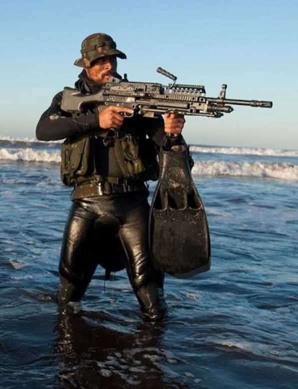 A man stands in the water with a big gun.