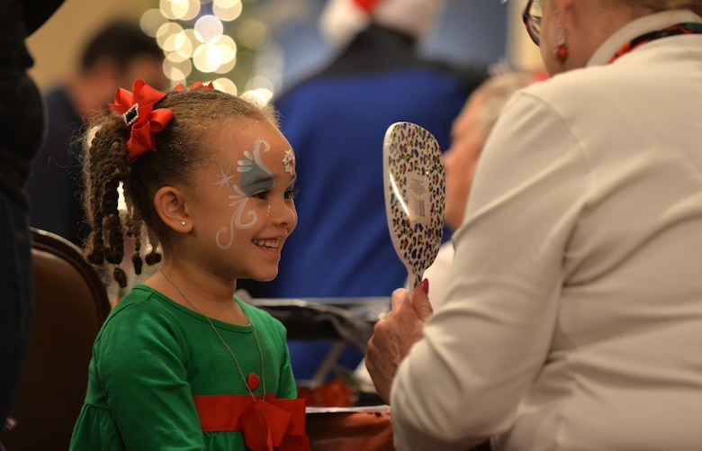 "Four-year-old Gabriella, daughter of Staff Sgt. Kevin Richardson, 55th Strategic Communication Squadron, looks at her reflection during the Offutt Christmas Tree Lighting event at the Patriot Club, Offutt Air Force Base, Nebraska, Dec. 6, 2018. The ceremony included a meet and greet with Mr. and Mrs. Claus, live music, dinner, bingo and an ""Elf Mart"" where children had a chance to shop for their parents. (U.S. Air Force photo by Josh Plueger)"