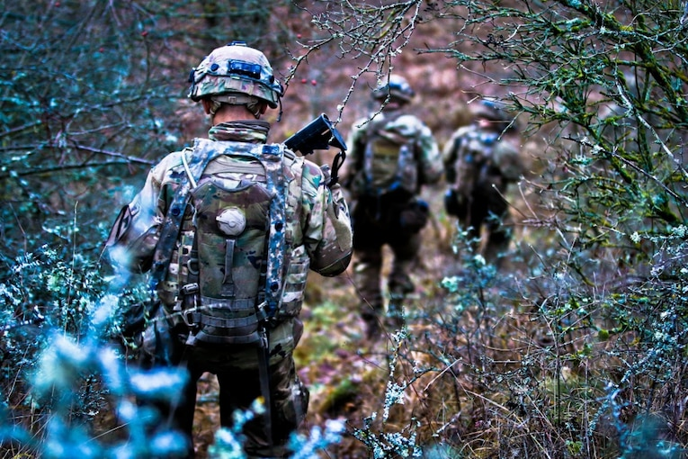 Soldiers walk through brush in a valley.