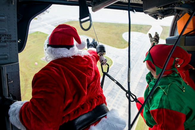 Santa and his elf waves to a crowd below during the 347th Rescue Group and 23d Maintenance Group Children's Christmas Party, Dec. 1, 2018, at Moody Air Force Base, Ga. Airmen and their families enjoyed the holiday festivities by taking photos with Santa, face painting and playing games. (U.S. Air Force photo by Airman 1st Class Erick Requadt)