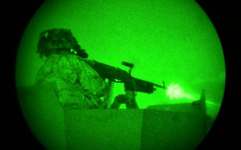 A solider shoots at targets with a machine gun under the night sky.
