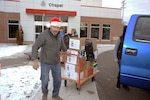 Don Phillips, DLA Installation Support at Battle Creek site director, pulls a cart full of donated items into the Salvation Army facility.