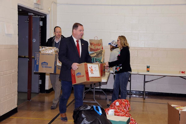 DLA Disposition Services Director Mike Cannon (center) carries a box of donations into the staging area as other volunteers take in more items.