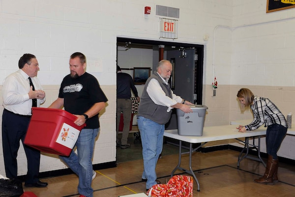 "Ray Zingaretti (far left), Logistics Information Services director; Mike Schmidt (left center), volunteer,  Kevin Faber (right center), local DLA Information Operations ""mayor;"" and LeAnn Gaviglio, delivery and volunteer coordinator, check in items and move them to the staging area."