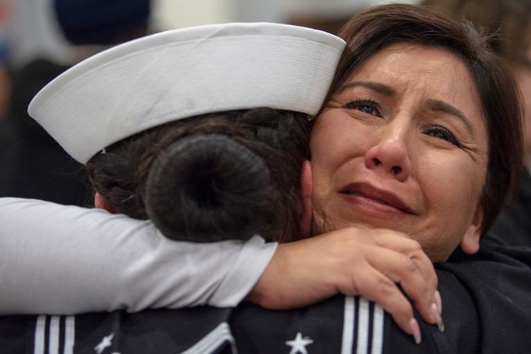 A sailor is hugged by a woman.