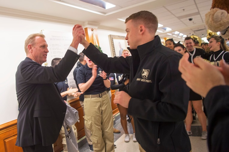 Deputy Defense Secretary Patrick M. Shanahan high-fives an athlete during a pep rally.