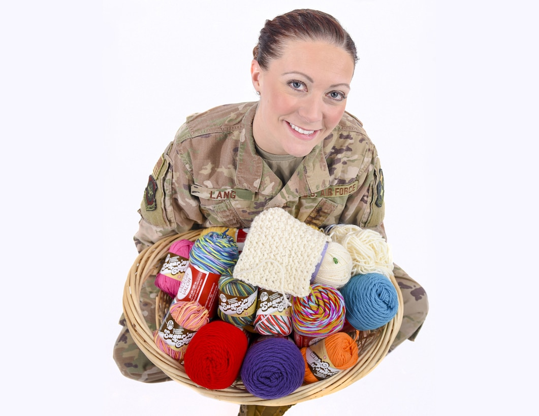 Tech. Sgt. Amber Lang poses for a photo holding a basket of yarn.