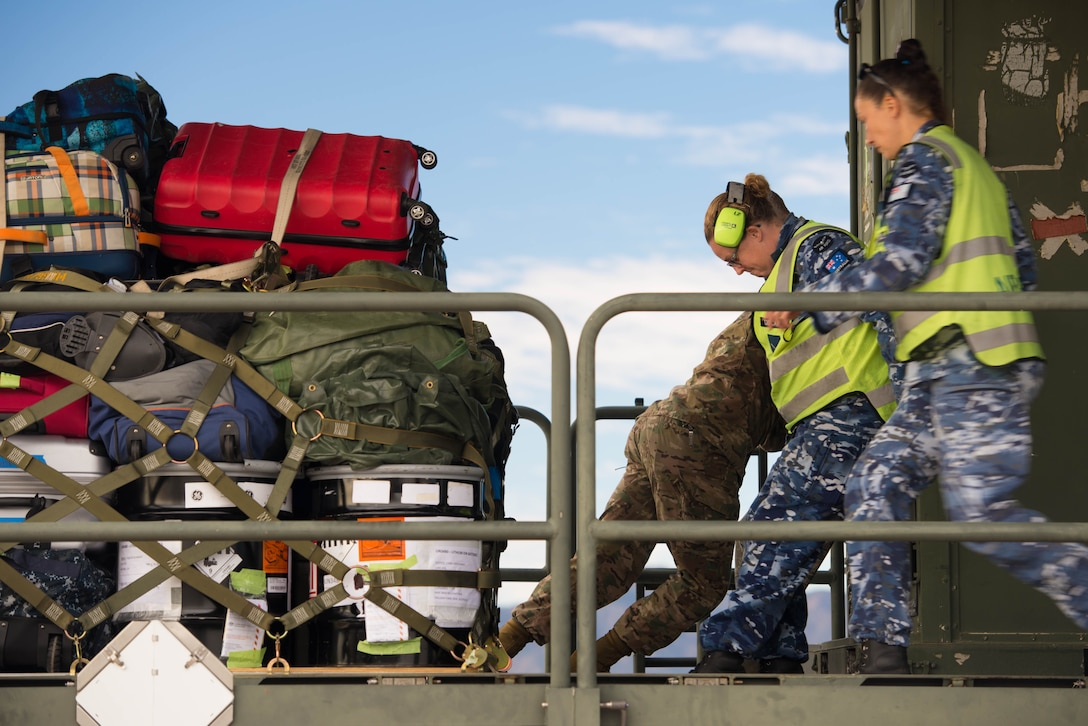 Royal Australian Air Force and U.S. Air Force push gear off of a K-Loader at Luke Air Force Base, Ariz., Dec. 3, 2018. The RAAF was preparing to launch two F-35A Lightning II's and a C-17 Globemaster III to start their historic journey to Australia. (U.S. Air Force photo by Staff Sgt. Jensen Stidham)