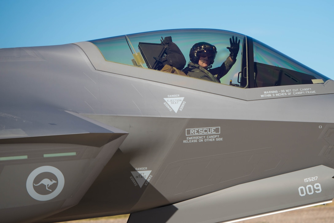 Royal Australian Air Force Wing Commander Darren Clare, F-35 pilot, waves goodbye while taxiing at Luke Air Force Base, Ariz., Dec. 3, 2018. The RAAF was preparing to launch two F-35A Lightning II's for their historic arrival in Australia several days later. (U.S. Air Force photo by Staff Sgt. Jensen Stidham)