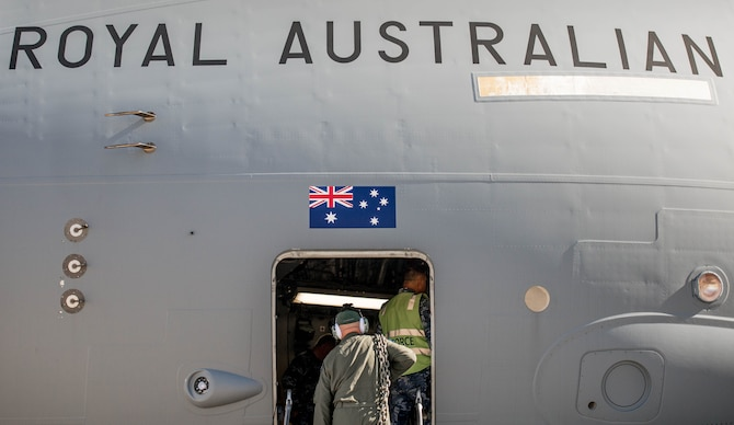 A Royal Australian Air Force airman carries supplies into a C-17 Globemaster III at Luke Air Force Base, Ariz., Dec. 3, 2018. The RAAF loaded the aircraft with airmen and supplies in preparation for their multi-day journey to Australia. The Globemaster is scheduled to follow two F-35A Lightning II's for their historic arrival in Australia. (U.S. Air Force photo by Staff Sgt. Jensen Stidham)