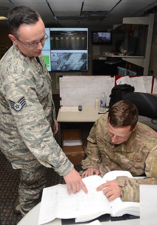 Staff Sgt. Curt Filkins II and Tech. Sgt. Chris Marek, with the Radar Operations Center in Norman, look up technical data of a radar system.