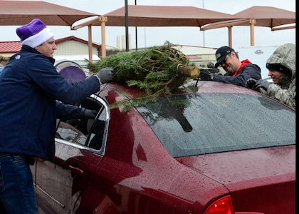 Maj. Lane Garman, 99th Flying Training Squadron, Director of Staff assists fellow volunteers, Mr. Robert Butler, Air Force Personnel Center, Human Resources and Capt. Jeromy McElwaney, 99th Flying Training, Squadron Executive, tie a tree down to a car during the Trees for Troops event at Joint Base San Antonio-Randolph, Texas, Dec. 7, 2018.