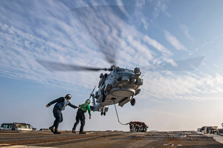 Two sailors move away from a hovering helicopter.