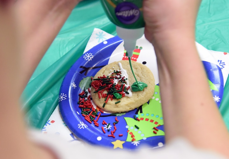 Caden Brazina, son of U.S. Air Force Staff Sgt. Stephen Brazina, 8th Medical Support Squadron, Kunsan Air Force Base, Korea, decorates a cookie during Christmas in the Park at Keesler Air Force Base, Mississippi, Dec. 6, 2018. The event hosted by Outdoor Recreation included cookie and ornament decorating, games and visits with Santa. (U.S. Air Force photo by Kemberly Groue)