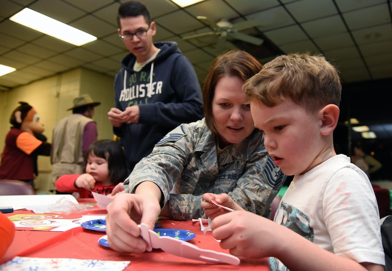 U.S. Air Force Master Sgt. Victoria Cortez, 81st Force Support Squadron Airman and Family Readiness Center NCO in charge, assists her son, Alex, with assembling an ornament during Christmas in the Park at Keesler Air Force Base, Mississippi, Dec. 6, 2018. The event hosted by Outdoor Recreation included cookie and ornament decorating, games and visits with Santa. (U.S. Air Force photo by Kemberly Groue)