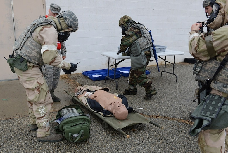Airmen in full mission oriented protective posture gear practice first aid on a casualty dummy during the latest readiness exercise Dec. 6. (U.S. Air Force photo by Kenji Thuloweit)