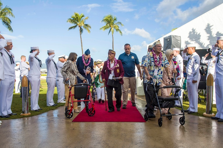 Sailors salute World War II veterans walking on a red carpet in front of palm trees.