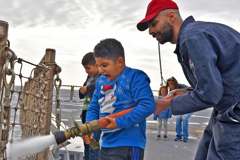 A sailor helps a child hold a fire hose on a ship.