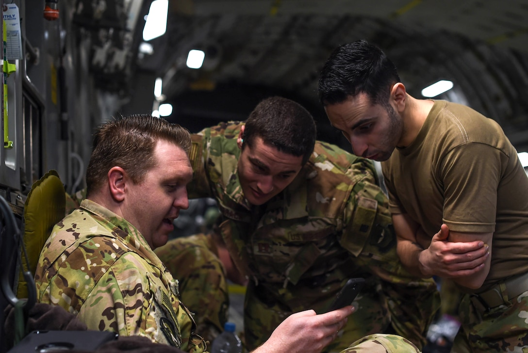 Staff Sgt. John Nieves Camacho, right, 627th Air Base Group religious affairs specialist, talks with Staff Sgt. Cameron Morris, left, 4th Airlift Squadron loadmaster, and Capt. Alexander Jobrack, middle, 62nd Medical Squadron flight surgeon, inside a C-17 Globemaster III at Rota Naval Station, Spain, Nov. 28, 2018. Camacho was part of a religious support team that flew with deploying and returning Airmen to offer any assistance they may need during the flights to and from Ali Al Salem Air Base, Kuwait, and Al Udeid Air Base, Qatar. (U.S. Air Force photo by Senior Airman Tryphena Mayhugh)