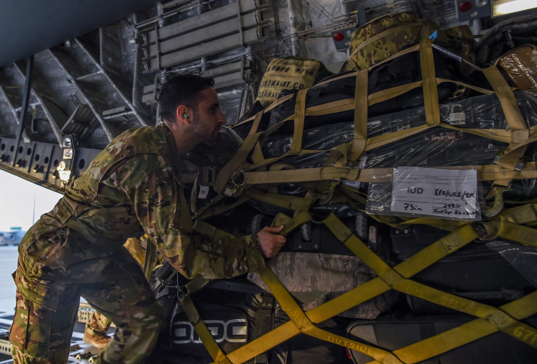 Staff Sgt. John Nieves Camacho, 627th Air Base Group religious affairs specialist, pushes a pallet of luggage onto a C-17 Globemaster III at Al Udeid Air Base, Qatar, Dec. 1, 2018. Camacho was part of a religious support team that flew with deploying and returning Airmen to offer any assistance they may need during the flights to and from Ali Al Salem Air Base, Kuwait, and Al Udeid Air Base, Qatar. He made an effort during the trip to also assist the aircrew any way that he could. (U.S. Air Force photo by Senior Airman Tryphena Mayhugh)