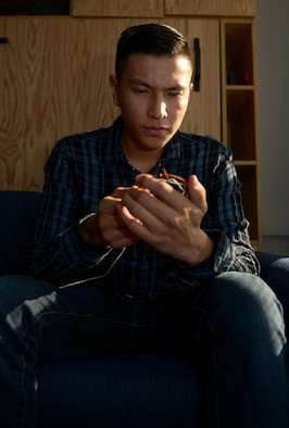 Airman 1st Class Phillip E. Rock weaves a dream catcher.