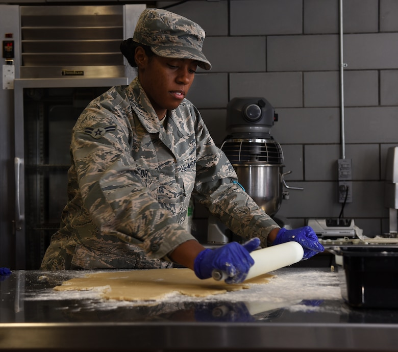 Airman 1st Class Alexis M. Taylor rolls dough for chocolate pudding pies.