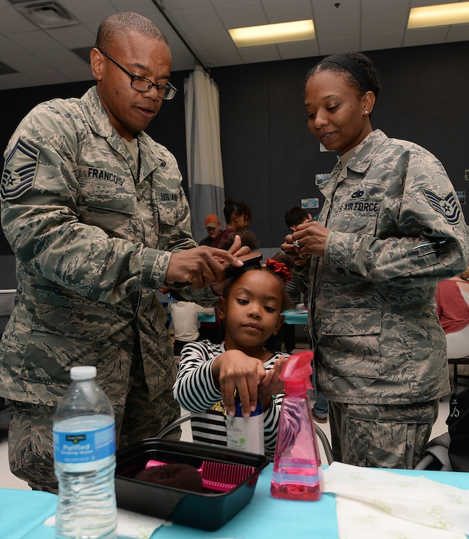Senior Master Sgt. Ed Francois and his wife Tech. Sgt. Brenda Francois style their daughter JazLynn's hair.