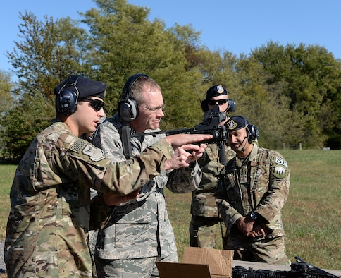 Senior Airman Anthony M. Bailey, a combat arms instructor assigned to the 509th Security Forces Squadron, familiarizes Maj. Gen. James C. Dawkins Jr., Eighth Air Force commander, with the M320 grenade launcher.
