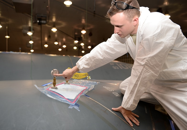 Senior Airman Austin K. Choate displays the tools used to vacuum seal tape on the B-2 Stealth Bomber.