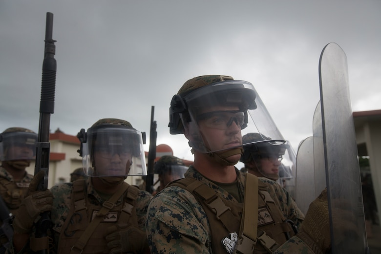 Lance Cpl. Nicholas S. Whitesall, a canonneer with Echo Battery, Battalion Landing Team, 1st Battalion, 4th Marines, and other Marines with the BLT wielding riot shields and Remington M1014 shotguns await further instructions during Noncombatant Evacuation Operations training at Camp Hansen, Okinawa, Japan, Dec. 6, 2018.