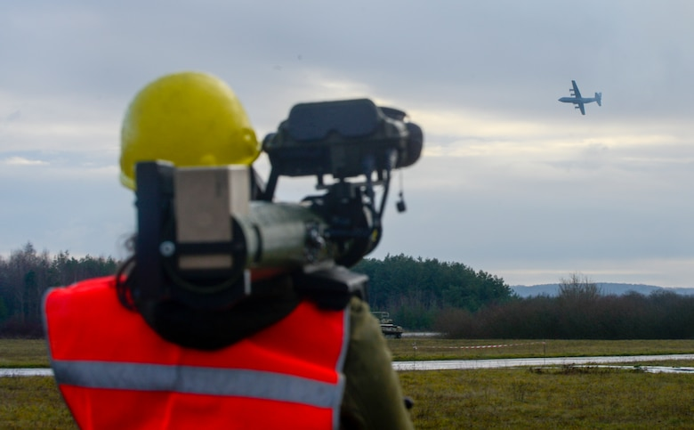 A Polygone employee uses a man-portable aircraft survivability trainer, or MAST, to simulate enemy fire for the aircrew of a C-130J Super Hercules aircraft assigned to the 37th Airlift Squadron, 86th Airlift Wing, Ramstein Air Base, Germany, during exercise Contested Forge on Grostenquin Air Base, France, Dec. 4, 2018. Contested Forge is an annual exercise that tests the 435th Contingency Response Group's ability to build a forward operating base and conduct airfield operations in an austere environment, friendly or hostile. (U.S. Air Force photo by Staff Sgt. Timothy Moore)