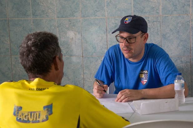 Jauier Andrade, a surgeon from New York City and a member of the Venezuelan American Medical Association, talks to a patient at one of two medical sites.