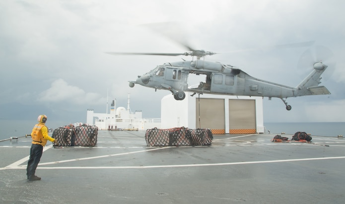 "An MH-60S Seahawk, assigned to the ""Sea Knights"" of Helicopter Sea Combat Squadron (HSC) 22, performs a vertical replenishment aboard the hospital ship USNS Comfort (T-AH 20)."
