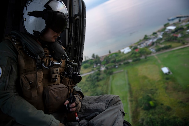 "Naval Aircrewman (Helicopter) 2nd Class Connor McSpadden, from Charlette, N.C., conducts a survey of the Honduran airspace in preparation for vertical replenishment operations from aboard an MH-60S Seahawk, assigned to the ""Sea Knights"" of Helicopter Sea Combat Squadron (HSC) 22."