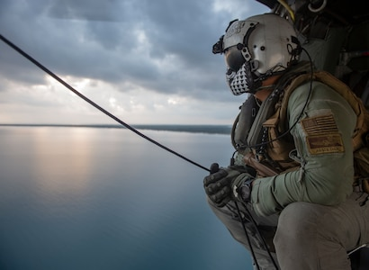 """Senior Chief Naval Aircrewman (Helicopter) Scott Chun, from Honolulu, conducts a survey of the Honduran airspace in preparation for vertical replenishment operations from aboard an MH-60S Seahawk, assigned to the """"Sea Knights"""" of Helicopter Sea Combat Squadron (HSC) 22."""