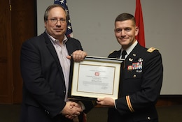 Lt. Col. Cullen Jones, U.S. Army Corps of Engineers Nashville District Commander, presents the Department of the Army Achievement Medal for Civilian Service to Travis A. Wiley, assistant program coordinator of the Nashville District's Leadership Development Program Level II Course, for his initiative in developing program contract requirements, organizing program schedules, making logistical arrangements for class sessions during the program's graduation ceremony Dec. 4, 2018 at the Scarritt Bennett Center in Nashville, Tenn. (USACE Photo by Lee Roberts)